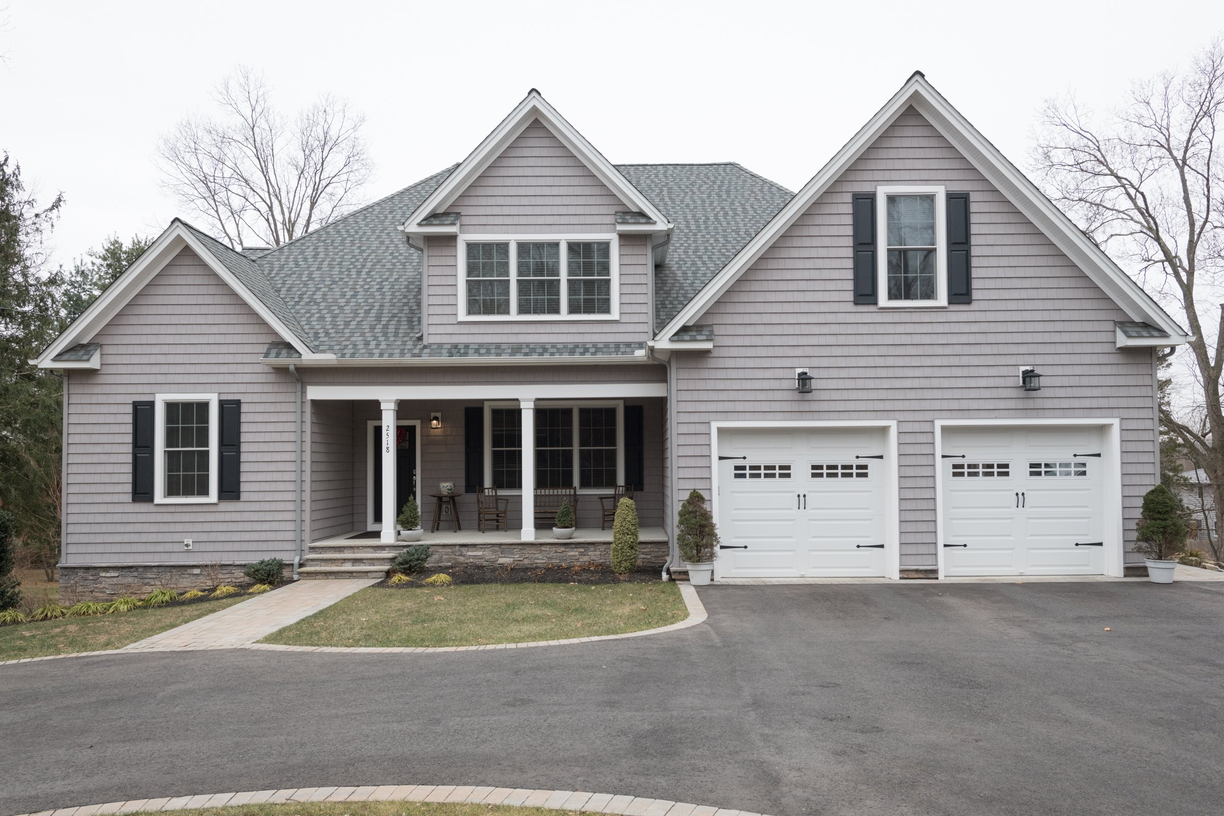 grey custom home with 2 white garages by GTG custom home builders in new jersey